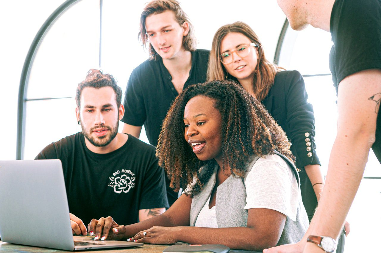 grupo de jovens que olham para um notebook sobre uma mesa