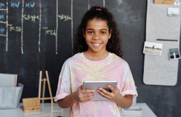 garota negra de cabelos longos sorri enqquanto segura um tablet na frente de um quadro negro (palavras de destaque: educação básica)