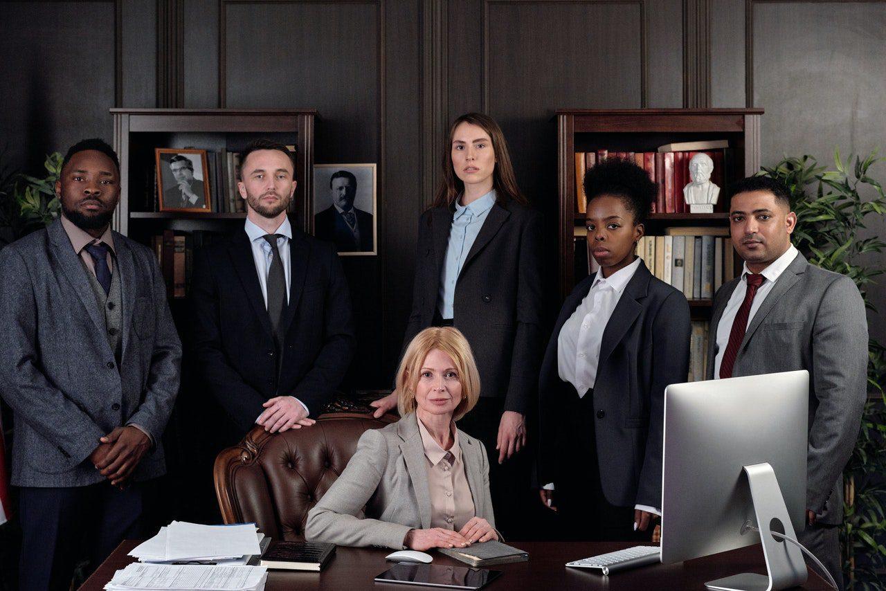 3 homens e 3 mulheres, em trajes formais, em escritório com parede de madeira e livros na estante