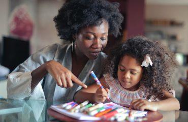 Mulher aponta desenho feito por menina negra ao seu lado