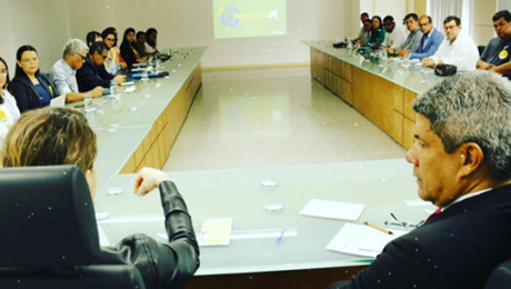 mesa em formato de u com várias pessoas em reunião