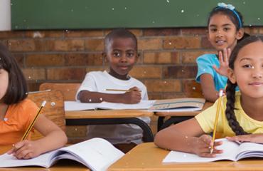 4 crianças em suas carteiras - doar educação 360