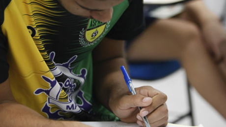 detalhe de jovem concentrado que escreve com caneta esferográfica
