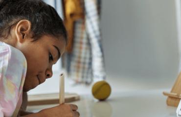 garota negra escreve com caneta numa mesa com tablet