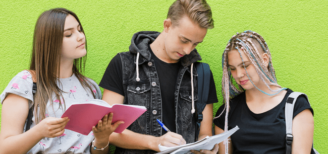 três jovens de pele clara lado a lado olham caderno