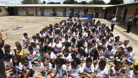 vários alunos sentados no pátio da escola