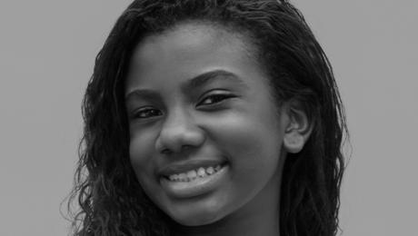 menina negra sorri de perfil