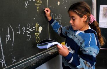 menina escreve no quadro negro enquanto olha para caderno em uma de suas mãos - ministro
