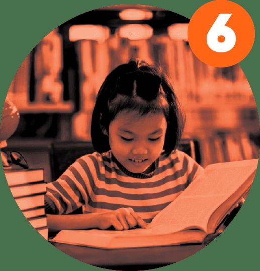 Aluna de origem asiática lê um livro com a ajuda do seu dedo indicador