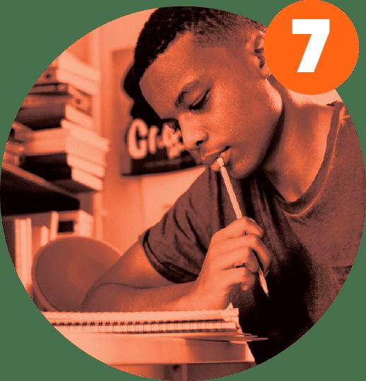 Aluno negro lê seu caderno e segura lápis junto aos lábios