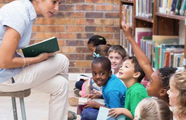professora sentada em banquinho lê para crianças sentadas ao chão