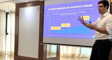 Olavo Nogueira Filho fala ao lado de telão sobre oportunidade de um novo fundeb