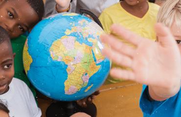 globo terrestre em meio a crianças