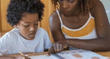 mulher e crianças negras olhando juntas para livro sobre mesa