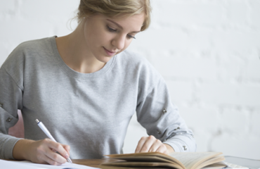 mulher de pele clara e cabelos presos escreve numa folha enquanto lê. Esse conteúdo fala sobre educação.