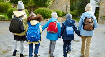 cinco crianças jovens caminham de mãos dadas agasalhadas e mochila nas costas