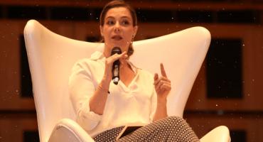 Presidente do Todos Priscila Cruz ao microfone sentada em cadeira branca