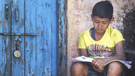 menino sentado ao lado de porta descascada azul de madeira com livro sobre seu colo - senado