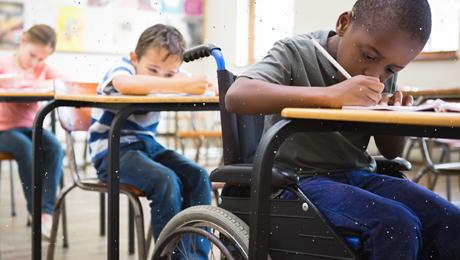 menino em cadeira de rodas escreve na sua carteira e colegas na fila detrás fazem o mesmo - esse conteúdo trata de educação formal