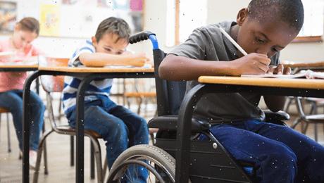 menino em cadeira de rodas escreve na sua carteira e colegas na fila detrás fazem o mesmo