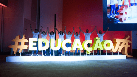 """oito pessoas de pé e mãos dadas erguidas atrás de painel com a frase """"educação já"""""""