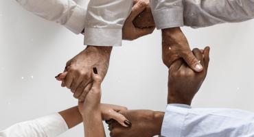 mãos de adultos entrelaçadas e formam um quadrado entre si