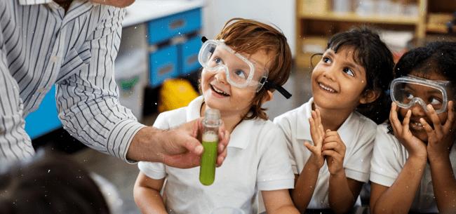 3 crianças sorriem e olham para professor enquanto ele mostra tudo de ensaio com líquido verde
