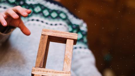 detalhe de mão de criança que se aproxima para tocar a torre de blocos de madeira - esse conteúdo fala sobre justiça educacional