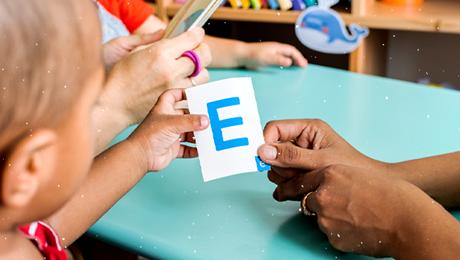 Detalhe de mão de professora que segura papel com letra E enquanto criança observa