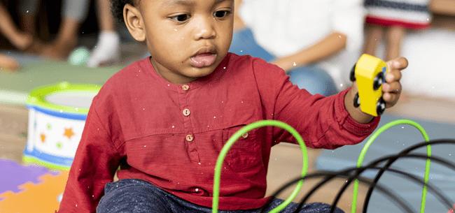 criança de uns 2 anos brinca com carrinho amarelo de madeira - IPTI