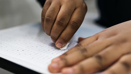 detalhe de mãos que usam borracha numa folha de respostas de prova