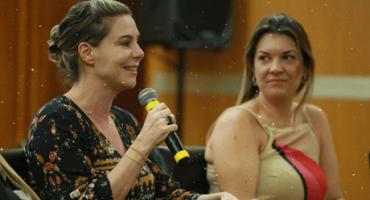 Priscila Cruz fala ao microfone enquanto é observada por mulher ao seu lado