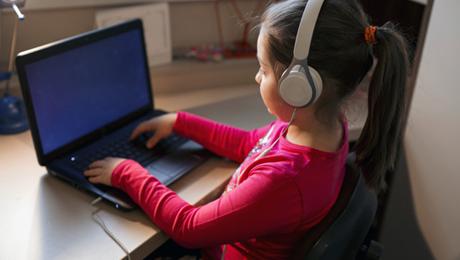 menina com fones de ouvido usa computador portátil