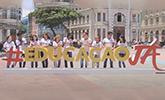 pessoas atrás de letras gigantes formando educação já no marco zero, recife