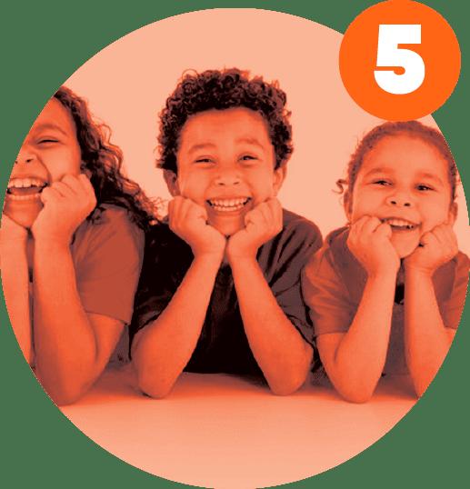 três crianças sorriem deitadas de bruço e queixos apoiados nas mãos