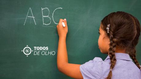 Menina escreve A, B e C no quadro negro