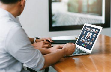 detalhes de duas pessoas na frente de um computador portátil sobre mesa de madeira