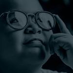 criança aponta dedo indicador nos seus óculos e olha para cima.