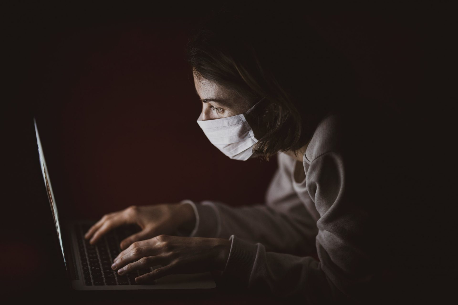 pessoa com máscara de proteção usa computador portátil na penumbra