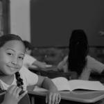 foto preta e branca de crianças em sala de aula e uma dela olha para a câmera. Esse conteúdo trata-se do Ministério da Educação.