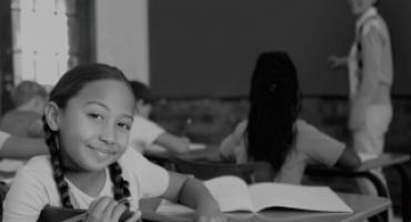 foto preta e branca de crianças em sala de aula e uma dela olha para a câmera.