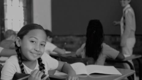 foto preta e branca de crianças em sala de aula e uma dela olha para a câmera. Esse conteúdo trata-se do Ministério da Educação e ensino.