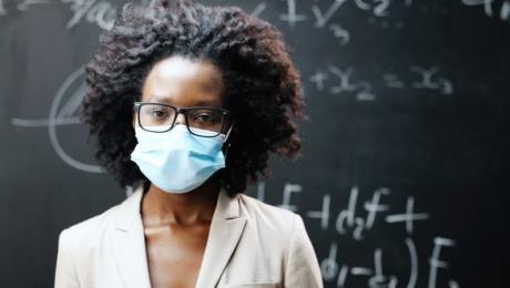professora negra de óculos usa máscara de proteção à frente do quadro negro