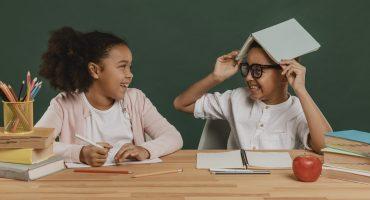 menina e menino se divertem com material escolar - ano de 2021