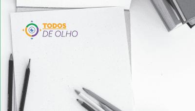 alguns lápis sobre uma folha em branco com logomarca Todos de Olho no topo
