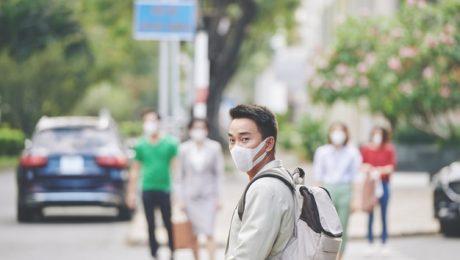Homem oriental e de máscara no rosto usando mochila e atravessando a rua para ir à escola