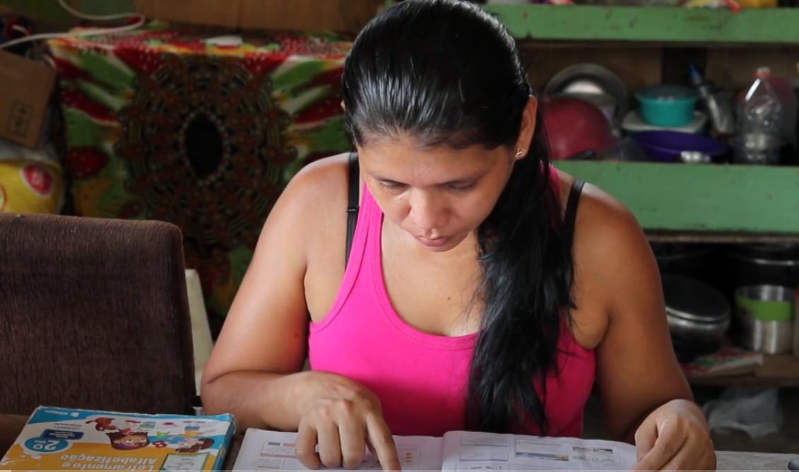 Mulher de cabelos pretos sentada em frente a uma mesa e lendo um livro escolar