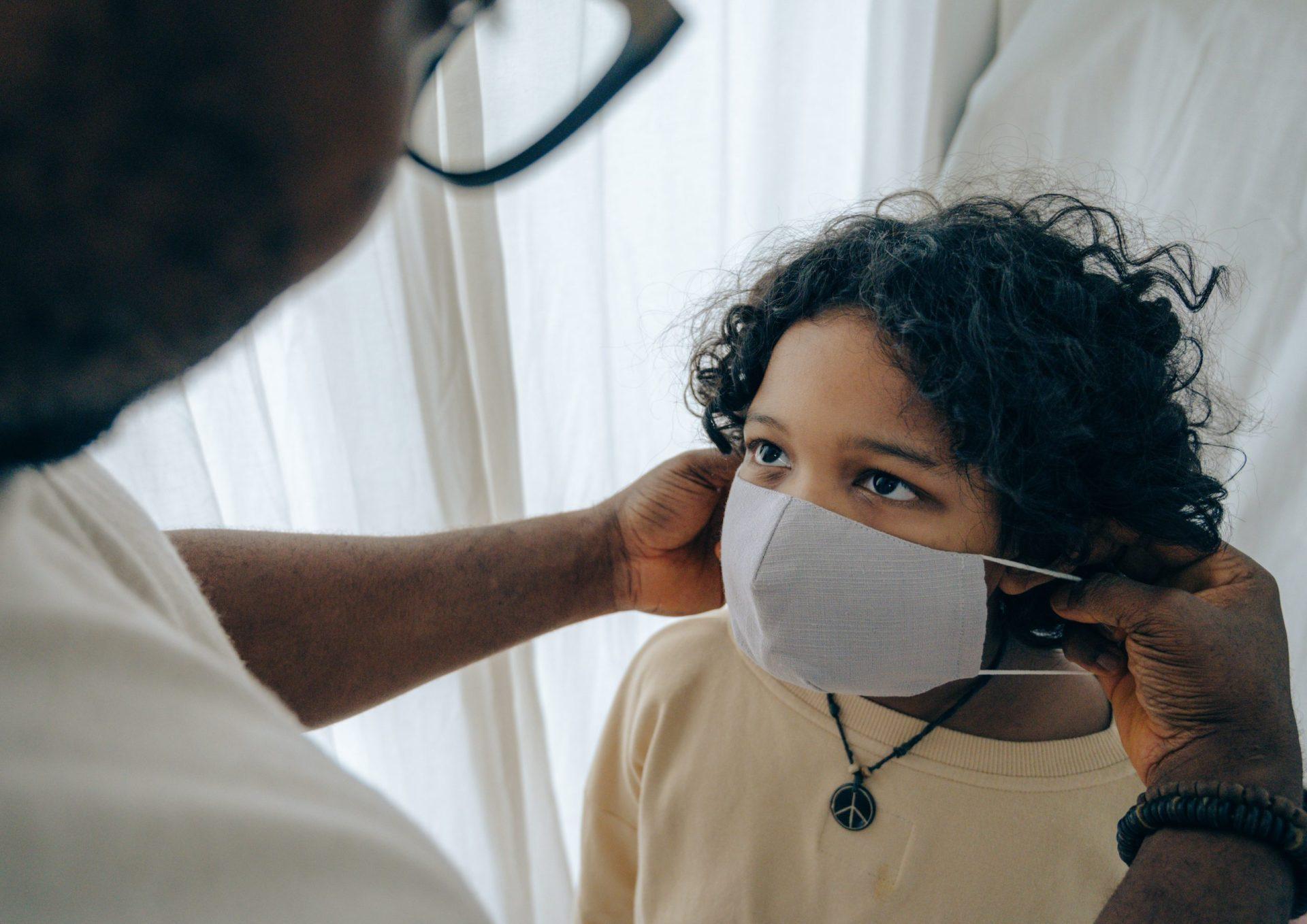 homem negro em primeiro plano coloca máscara facial cinza no rosto de uma criança negra
