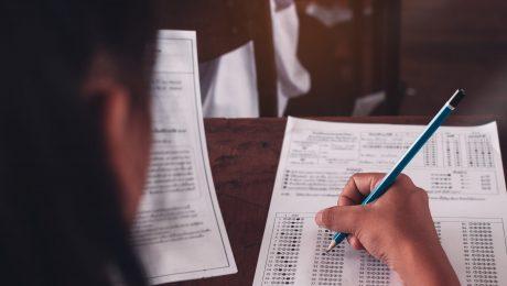 Estudante sentado em sala de aula fazendo prova