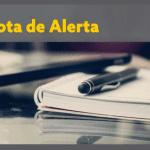 """caneta sobre caderno e título em amarelo """"Nota de Alerta"""""""